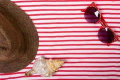 Vacaciones de verano, turismo, viaje, concepto del día de fiesta Cáscaras del mar, sombrero de la playa y manta rayada en blanco  Imágenes de archivo libres de regalías