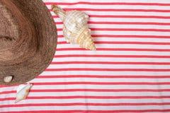 Vacaciones de verano, turismo, viaje, concepto del día de fiesta Cáscaras del mar, sombrero de la playa y manta rayada en blanco  Foto de archivo libre de regalías