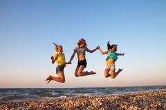 Vacaciones de verano y vacaciones - muchachas que saltan encendido Imagen de archivo