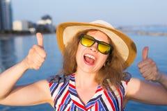 Vacaciones de verano y vacaciones - mujer joven que muestra los pulgares para arriba en la playa Imagen de archivo