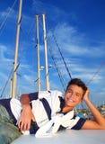 Vacaciones del adolescente del muchacho que ponen la sonrisa del barco del puerto deportivo Imagen de archivo libre de regalías