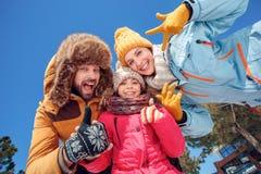 Vacaciones del invierno Tiempo de la familia juntos al aire libre que muestra los pulgares encima de la visión inferior alegre imagen de archivo libre de regalías