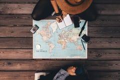 Vacaciones del planeamiento de los pares que se sientan por el mapa del mundo Fotos de archivo
