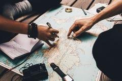 Vacaciones del planeamiento de los pares usando el mapa del mundo Foto de archivo libre de regalías