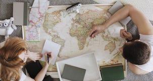 Vacaciones del planeamiento del hombre y de la mujer usando un mapa del mundo y otros accesorios del viaje Mujer que observa los  almacen de video
