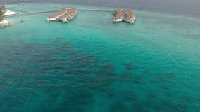 Vacaciones exóticas costosas, volando sobre casas de planta baja del agua del centro turístico en el mar de la turquesa en verano almacen de metraje de vídeo
