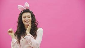 Vacaciones festivas de Pascua Mujer joven sonriente en oídos del conejito de pascua en el fondo rosado que salta y que mira la co