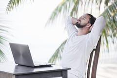 Vacaciones y tecnolog?a Trabajo y viaje Hombre barbudo joven usando el ordenador portátil mientras que se sienta en la barra del  imágenes de archivo libres de regalías
