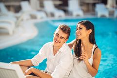 Vacances affectueuses de dépense de couples sur la piscine tropicale de station de vacances Lune de miel de nouveaux mariés sur l photo stock