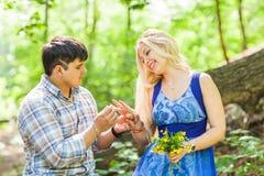 Vacances, amour, couples, relations et concept de datation - homme romantique proposant à une femme en parc d'été Images stock