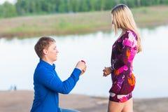 Vacances, amour, couples, relations et concept de datation - homme romantique proposant à une femme sur la nature Photos stock