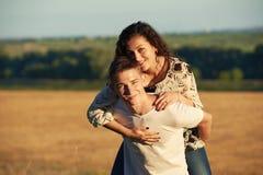 Vacances, augmentant, concept d'amour et d'amitié - couple de sourire ayant l'amusement au-dessus du fond de ciel de soirée, sais Images stock