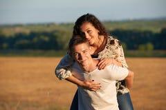 Vacances, augmentant, concept d'amour et d'amitié - couple de sourire ayant l'amusement au-dessus du fond de ciel de soirée, sais Photo stock