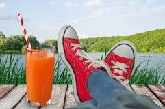 Vacances avec des vues de l'eau et des bois avec un verre de ju Images libres de droits