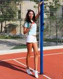 Vacances Brune aux jambes longues bronzée incroyable dans des shorts blancs, une chemise de turquoise et des espadrilles blanches Photo libre de droits