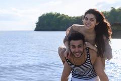 Vacances d'été de plage de couples, homme de Carry Woman Beautiful Young Happy d'homme et sourire de femme photographie stock libre de droits