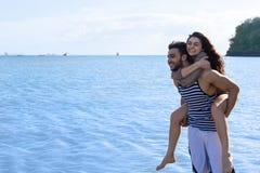 Vacances d'été de plage de couples, homme de Carry Woman Beautiful Young Happy d'homme et sourire de femme image libre de droits
