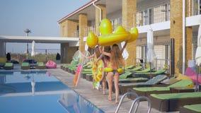 Vacances d'été, jeunes femmes avec de longs cheveux et corps bronzés minces ayant l'amusement à la réception au bord de la piscin banque de vidéos