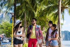 Vacances d'été parlantes de marche de mer de vacances de plage de groupe des jeunes d'amis tropicaux de palmiers Photo libre de droits