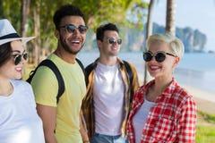 Vacances d'été parlantes de marche de mer de vacances de plage de groupe des jeunes d'amis tropicaux de palmiers Image libre de droits