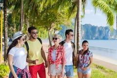 Vacances d'été parlantes de marche de mer de vacances de plage de groupe des jeunes d'amis tropicaux de palmiers Photographie stock libre de droits