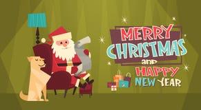 Vacances d'hiver de list d'envie de lecture de chapeau de Santa Claus With Dog In Red de carte de voeux de Joyeux Noël et de bonn Photographie stock