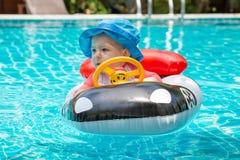 Vacances d'?t? en mer Une petite fille moins que d'un an conduit un bateau gonflable sous forme de voiture Dans la piscine image libre de droits