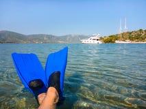 Vacances de bien-être d'été par le concept de mer, pieds en FIN sur la plage de l'île de Poros de baie d'amour, Agrosaronikos, Gr Images libres de droits