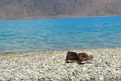Vacances de dépense sur la rive avec de l'eau bleu Images stock