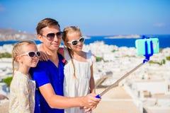 Vacances de famille en Europe Père et enfants prenant la ville de Mykonos de fond de selfie en Grèce Images stock