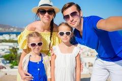 Vacances de famille en Europe Parents et enfants prenant la ville de Mykonos de fond de selfie en Grèce Photographie stock libre de droits
