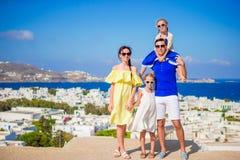 Vacances de famille en Europe Parents et enfants regardant l'île de Mykonos de fond d'appareil-photo en Grèce Image libre de droits