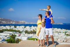 Vacances de famille en Europe Parents et enfants regardant le paysage urbain de l'île de Mykonos en Grèce Image libre de droits
