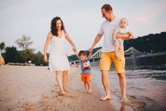 Vacances de famille en ?t? Jeune pied caucasien de famille marchant la plage sablonneuse aux pieds nus, eau de rivi?re de rivage  image libre de droits