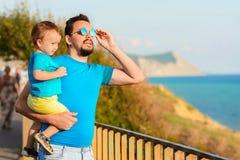 Vacances de famille et concept de voyage : le père et peu de fils regardent quelque chose qui se tient sur le remblai sur un bord photos stock