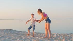 Vacances de famille La maman et le fils heureux dupent autour sur la plage contre le contexte de la mer clips vidéos