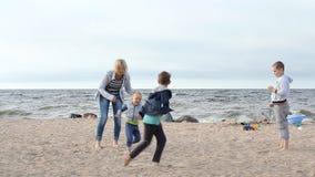 Vacances de famille sur l'océan - une jeune femme avec des enfants courant autour, jouant et gambadant banque de vidéos