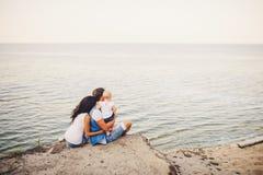 Vacances de famille de thème avec le petit enfant sur la nature et la mer La maman, le papa et la fille d'un an s'asseyent dans l Images stock