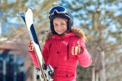Vacances de l'hiver Fille dans les lunettes et casque avec des skis tenant le pouce de représentation heureux dehors de sourire v images libres de droits