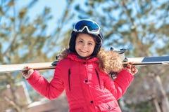 Vacances de l'hiver La fille dans les lunettes et le casque avec des skis derrière tenir le plan rapproché enthousiaste dehors de photos stock