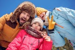 Vacances de l'hiver Temps de famille grimaçant ensemble dehors à la caméra riant le plan rapproché espiègle de vue inférieure photographie stock