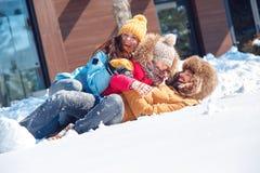 Vacances de l'hiver Temps de famille se trouvant ensemble dehors sur rire de neige espiègle image libre de droits