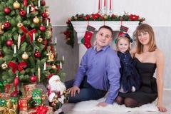 Vacances de Noël heureux Jeune famille à l'arbre de Noël avec une cheminée La fille embrasse les parents Images stock