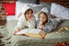 Vacances de Noël Le frère et la soeur s'étendent sur un lit dans des pyjamas mous Images stock