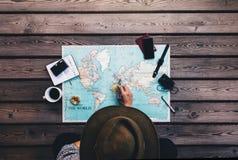 Vacances de planification de touristes utilisant la carte du monde Images libres de droits