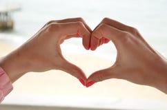 Vacances de romance de symbole de mer d'amour de mains Photo stock