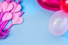 Vacances de Saint Valentin pailles à boire roses lumineuses avec des coeurs et des ballons colorés sur le fond bleu pailles sirot Images libres de droits