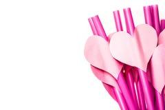 Vacances de Saint Valentin pailles à boire roses lumineuses avec des coeurs et un ruban rose dans un verre d'isolement sur le bla Photos stock