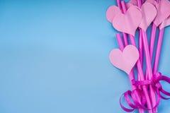 Vacances de Saint Valentin rose lumineux et pailles à boire bleues avec des coeurs et un ruban rose sur le bleu pailles sirotante Photo stock