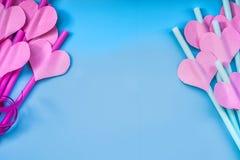 Vacances de Saint Valentin rose lumineux et pailles à boire bleues avec des coeurs et un ruban rose sur le bleu pailles sirotante Photos stock